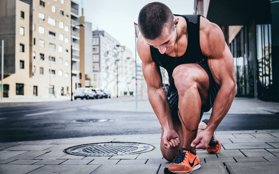 Male athlete lacing up his tennis shoes to prepare for a run in the city.