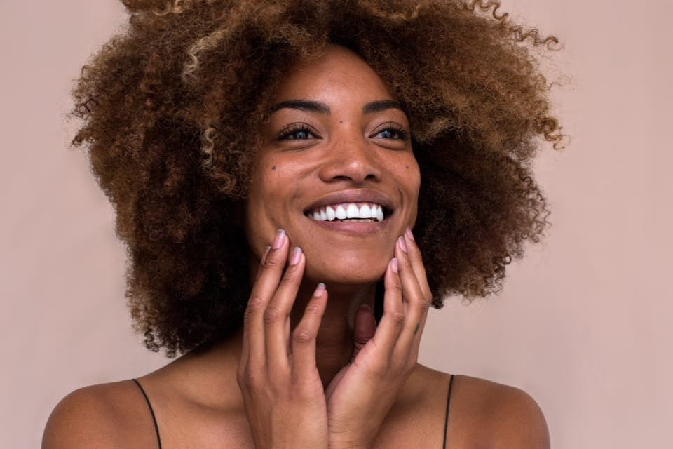 Beautiful smiling woman with healthy hair rich in biotin.