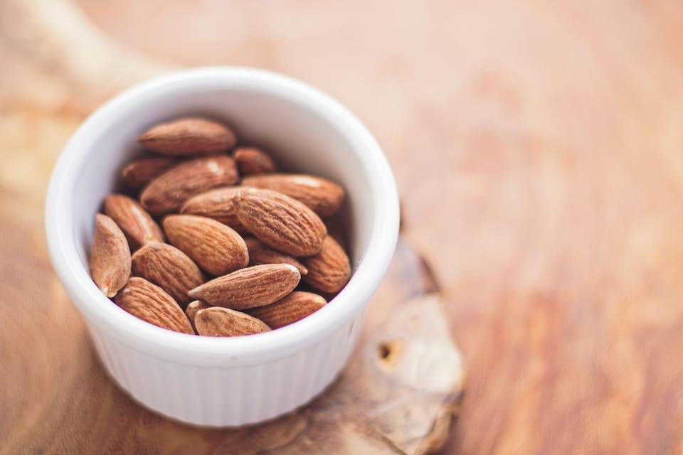 Ceramic bowl full of healthy, magnesium-rich almonds.