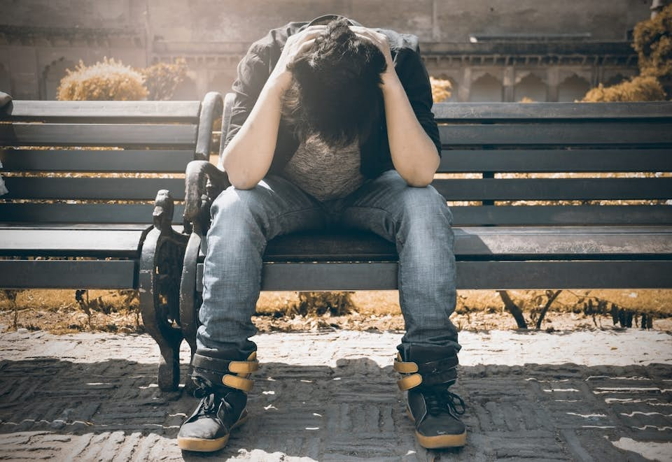 Depressed young man sitting on a park bench with his head in his hands.