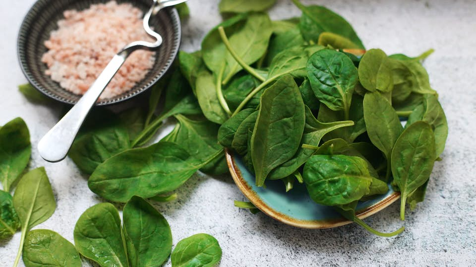 Folate-rich spinach and leafy greens in a blue ceramic bowl.
