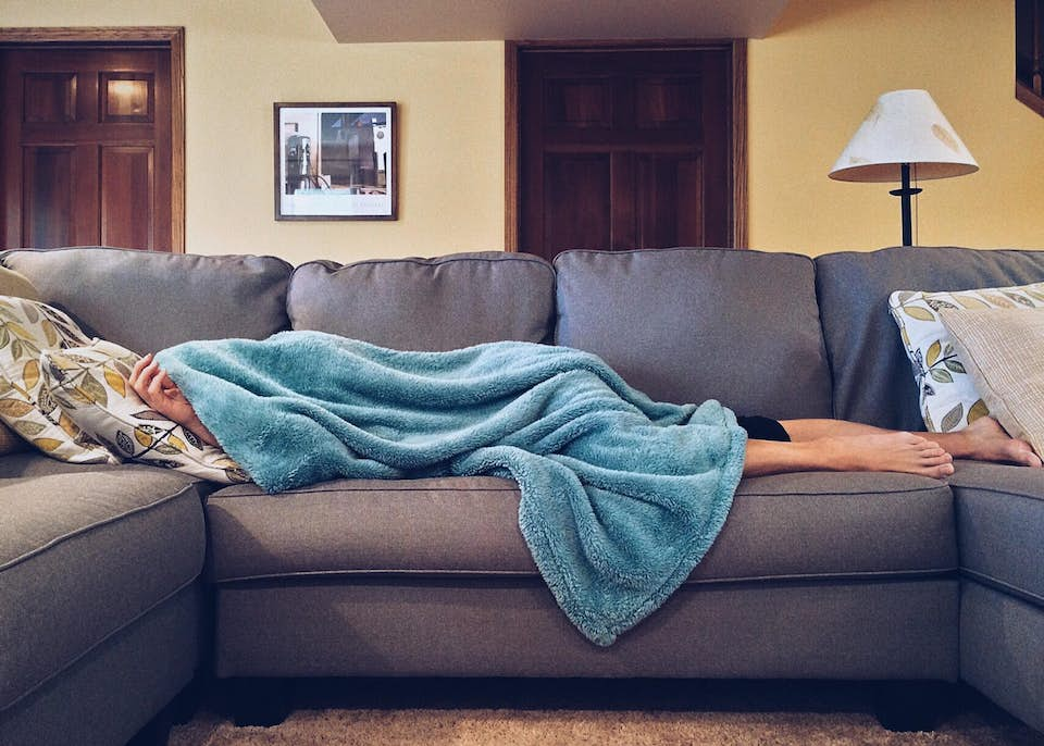 Hungover woman lying on the couch with a fuzzy blue blanket.
