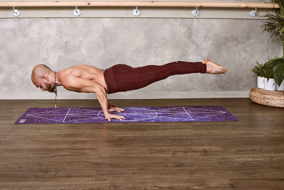 Strong, healthy man holding a difficult yoga pose on a purple yoga mat.