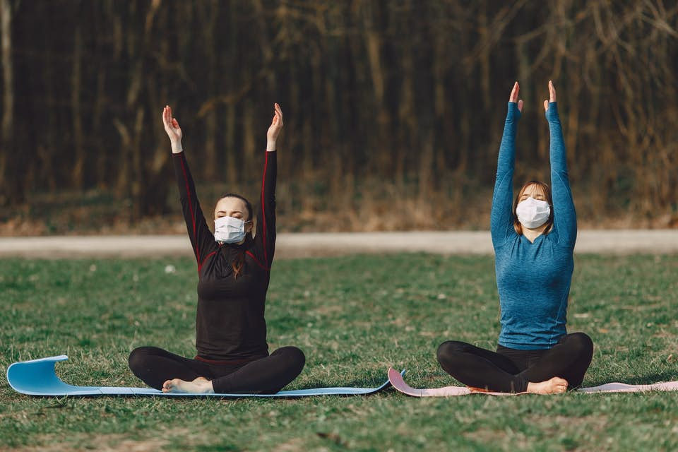 two women wearing masks detoxify with yoga in the park