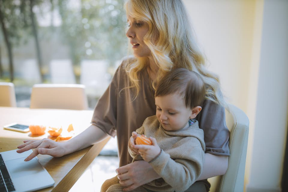 Woman working from home with baby eating a vitamin c orange