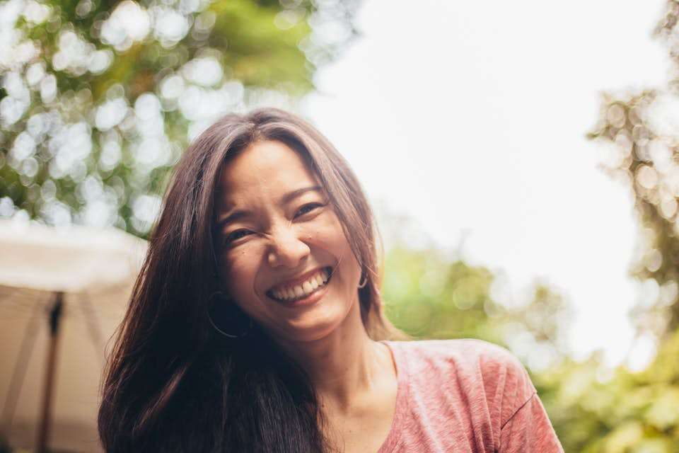 Happy middle-aged woman with long dark hair smiling at the camera.